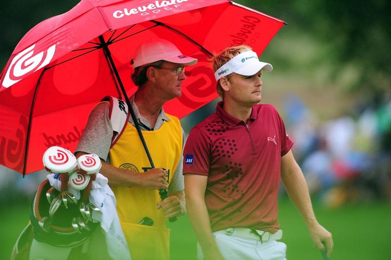 CHASKA, MN - AUGUST 16:  Soren Kjeldsen of Denmark (R) walks alongside his caddie Kevin Woodword under and umbrella on the first fairway during the final round of the 91st PGA Championship at Hazeltine National Golf Club on August 16, 2009 in Chaska, Minnesota.  (Photo by Stuart Franklin/Getty Images)