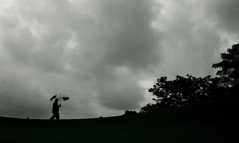 SYDNEY, AUSTRALIA - DECEMBER 12: A caddie takes shelter under an umbrella on the first tee during the second round of the 2008 Australian Open at The Royal Sydney Golf Club on December 12, 2008 in Sydney, Australia. (Photo by Mark Nolan/Getty Images)