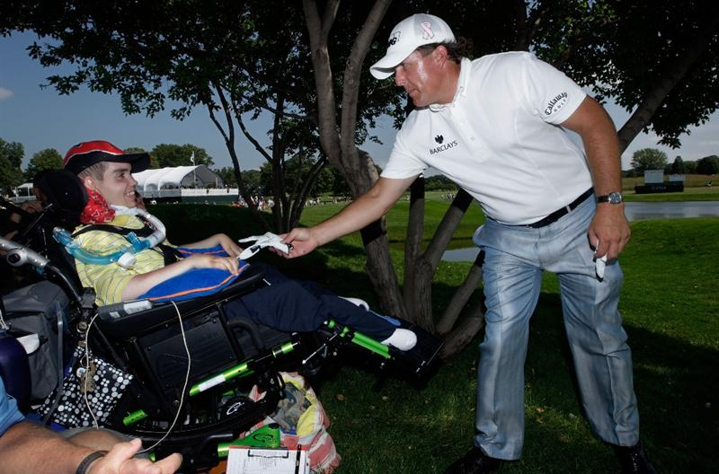 CHASKA, MN - AUGUST 12:  Phil Mickelson signs his glove and gives it to fan Adam Stenner of Milwaukee during the third preview day of the 91st PGA Championship at Hazeltine National Golf Club on August 12, 2009 in Chaska, Minnesota.  (Photo by Jamie Squire/Getty Images)