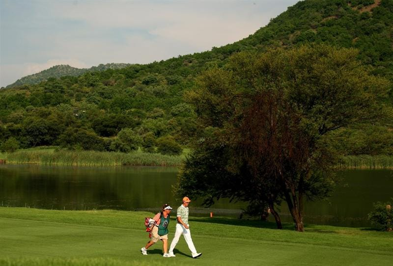 SUN CITY, SOUTH AFRICA - DECEMBER 06:  Henrik Stenson of Sweden and caddy Fanny Suneson walk down the 17th fairway during the third round of the Nedbank Golf Challenge at the Gary Player Country Club on December 6, 2008 in Sun City, South Africa.  (Photo by Richard Heathcote/Getty Images)
