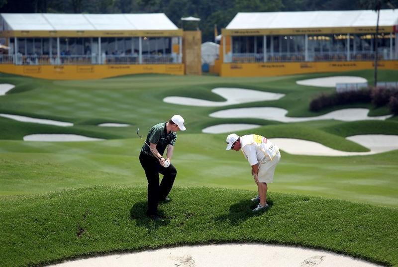 KUALA LUMPUR, MALAYSIA - MARCH 05:  Stephen Gallacher of Scotland prepares to hit his second shot on the 18th hole during the the second round of the Maybank Malaysian Open at the Kuala Lumpur Golf and Country Club on March 5, 2010 in Kuala Lumpur, Malaysia.  (Photo by Andrew Redington/Getty Images)