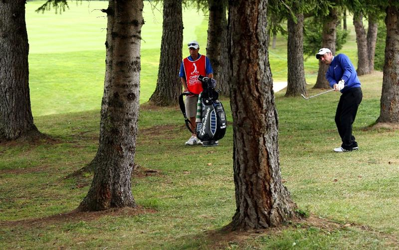 CRANS, SWITZERLAND - SEPTEMBER 04:  Paul McGinley of Ireland plays from out of the trees on the 14th hole during the second round of The Omega European Masters at Crans-Sur-Sierre Golf Club on September 4, 2009 in Crans Montana, Switzerland.  (Photo by Andrew Redington/Getty Images)