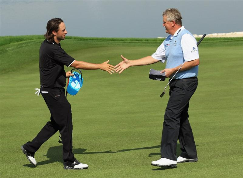 BAHRAIN, BAHRAIN - JANUARY 30:  Martin Wiegele of Austria (left) shakes hands with Colin Montgomerie of Scotland on the 18th hole during the final round of the Volvo Golf Champions at The Royal Golf Club on January 30, 2011 in Bahrain, Bahrain.  (Photo by Andrew Redington/Getty Images)