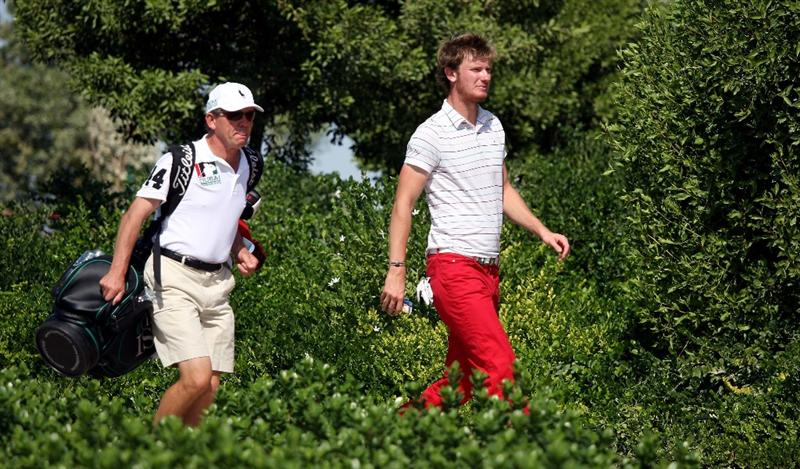 DUBAI, UNITED ARAB EMIRATES - NOVEMBER 19:  Chris Wood of England walks with his caddie Dave McNeilly on the 16th hole during the first round of the Dubai World Championship on the Earth Course, Jumeirah Golf Estates on November 19, 2009 in Dubai, United Arab Emirates.  (Photo by Andrew Redington/Getty Images)