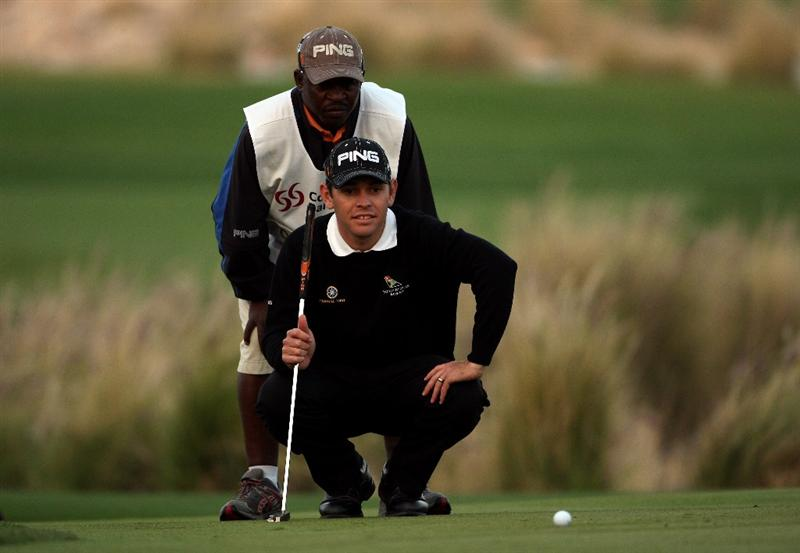 DOHA, QATAR - JANUARY 23:  Louis Oosthuizen of South Africa lines up a putt with his caddie Zack on the 18h hole during the second round of  the Commercialbank Qatar Masters at Doha Golf Club on January 23, 2009 in Doha, Qatar.  (Photo by Andrew Redington/Getty Images)