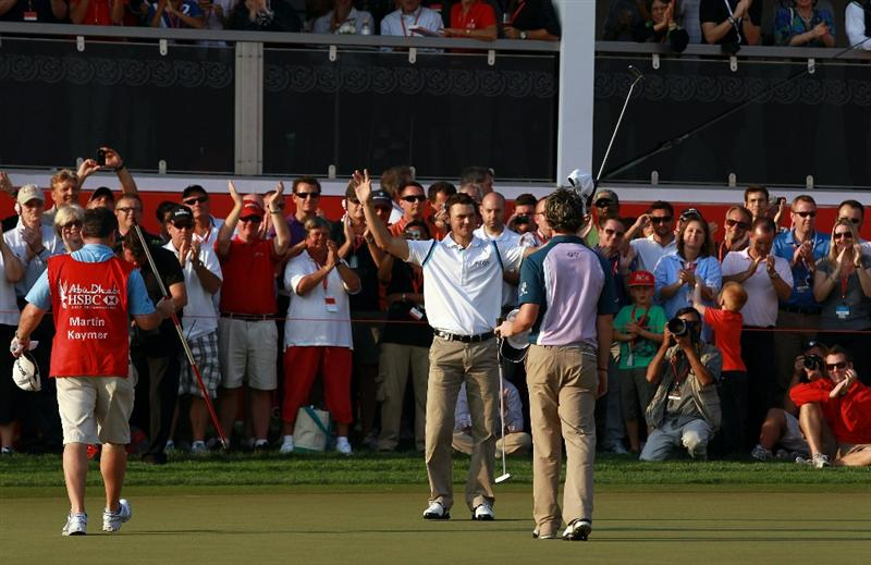 ABU DHABI, UNITED ARAB EMIRATES - JANUARY 23:  Martin Kaymer of Germany holds his arm aloft in victory as his playing partner Rory McIlroy moves to shake his hand on the 18th green during the final round of the 2011 Abu Dhabi HSBC Golf Championship held at the Abu Dhabi Golf Club on January 23, 2011 in Abu Dhabi, United Arab Emirates.  (Photo by David Cannon/Getty Images)