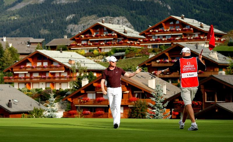 CRANS, SWITZERLAND - SEPTEMBER 04:  Simon Dyson of England hands his putter to his caddie on the 14th hole during the second round of The Omega European Masters at Crans-Sur-Sierre Golf Club on September 4, 2009 in Crans Montana, Switzerland.  (Photo by Andrew Redington/Getty Images)