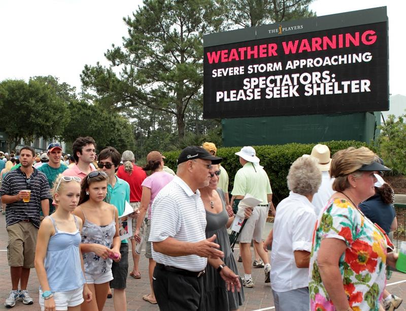 PONTE VEDRA BEACH, FL - MAY 14:  Fans walk past a warning sign after play was suspended due to severe storms during the third round of THE PLAYERS Championship held at THE PLAYERS Stadium course at TPC Sawgrass on May 14, 2011 in Ponte Vedra Beach, Florida.  (Photo by Scott Halleran/Getty Images)