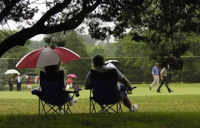 Under the cover of an umbrella, fans watch the action during the second round of the Commerce Bank Championship on the Red Course at Eisenhower Park in East Meadow, New York, on June 24, 2006.Photo by Steve Levin/WireImage.com