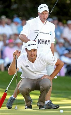 VIRGINIA WATER, ENGLAND - MAY 23:  Simon Khan of England lines up a putt on the 18th green with his caddie during the final round of the BMW PGA Championship on the West Course at Wentworth on May 23, 2010 in Virginia Water, England.  (Photo by Andrew Redington/Getty Images)