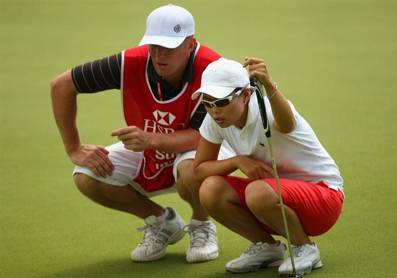 SINGAPORE - MARCH 08:  Sun Young Yoo of South Korea lines up a putt with her caddie on the third hole during the final round of the HSBC Women's Champions at Tanah Merah Country Club on March 8, 2009 in Singapore.  (Photo by Andrew Redington/Getty Images)