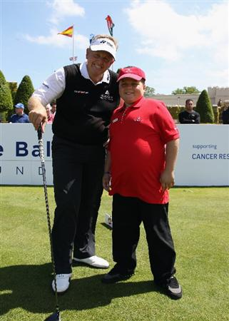 VIRGINIA WATER, ENGLAND - MAY 23:  Colin Montgomerie of Scotland poses with 11-year old Harry Moseley on the first hole during the 'Ole Seve' Pro-Am in aid of the Seve Ballesteros Foundation at Wentworth Club on May 23, 2011 in Virginia Water, England.  (Photo by Andrew Redington/Getty Images)