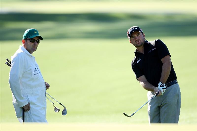 AUGUSTA, GA - APRIL 04:  Graeme McDowell of Northern Ireland hits a shot as his caddie Ken Comboy looks on during a practice round prior to the 2011 Masters Tournament at Augusta National Golf Club on April 4, 2011 in Augusta, Georgia.  (Photo by Andrew Redington/Getty Images)