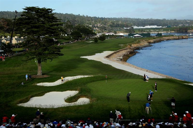PEBBLE BEACH, CA - JUNE 17:  Tiger Woods plays his shot on the 18th green as Ernie Els of South Africa looks on during the first round of the 110th U.S. Open at Pebble Beach Golf Links on June 17, 2010 in Pebble Beach, California.  (Photo by Donald Miralle/Getty Images)