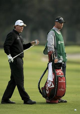 PACIFIC PALISADES, CA - FEBRUARY 18:  Phil Mickelson selects a club with caddie Jim MacKay on the second hole during the second round of the Northern Trust Open at the Riviera Country Club on February 18, 2011 in Pacific Palisades, California.  (Photo by Harry How/Getty Images)