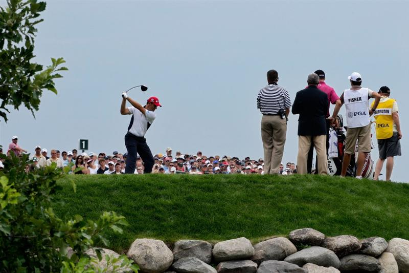CHASKA, MN - AUGUST 15:  Padraig Harrington of Ireland hits his tee shot on the first hole as Ross Fisher of England and their caddies look on during the third round of the 91st PGA Championship at Hazeltine National Golf Club on August 15, 2009 in Chaska, Minnesota.  (Photo by Jamie Squire/Getty Images)