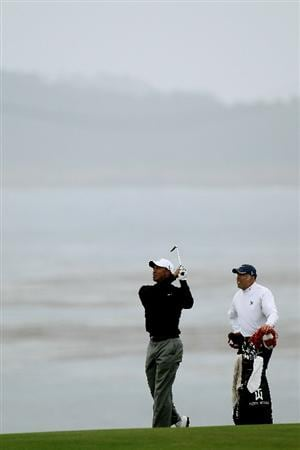 PEBBLE BEACH, CA - JUNE 15:  Tiger Woods hits a shot as his caddie Steve Williams looks on during a practice round prior to the start of the 110th U.S. Open at Pebble Beach Golf Links on June 15, 2010 in Pebble Beach, California.  (Photo by Stephen Dunn/Getty Images)