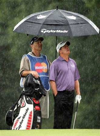 SUNNINGDALE, ENGLAND - JULY 24:  Fred Funk of the USA and his caddie wait in the rain on the ninth hole during the second round of The Senior Open Championship presented by MasterCard held on the Old Course at Sunningdale Golf Club on July 24, 2009 in Sunningdale, England.  (Photo by Andrew Redington/Getty Images)