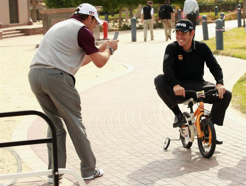 ABU DHABI, UNITED ARAB EMIRATES - JANUARY 18:  Lee Westwood of England, the World number one, (left) photographs Louis Oosthuizen of South Africa, the Open Champion, on a small bicycle at the Abu Dhabi Golf Club on January 18, 2011 in Abu Dhabi, United Arab Emirates.  (Photo by Andrew Redington/Getty Images)