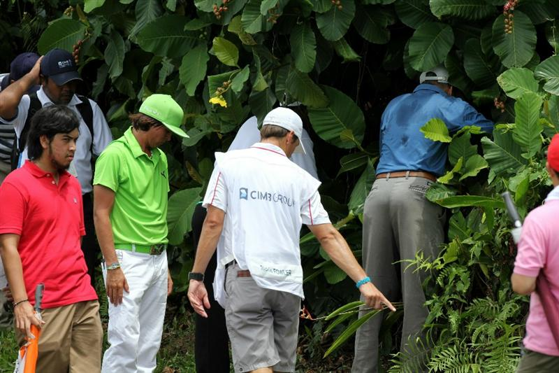 KUALA LUMPUR, MALAYSIA - OCTOBER 30: Rickie Fowler of USA and his caddie gets help from the spectators in search of his missing ball on the 9th hole during day three of the CIMB Asia Pacific Classic at The MINES Resort & Golf Club on October 30, 2010 in Kuala Lumpur, Malaysia. (Photo by Stanley Chou/Getty Images)