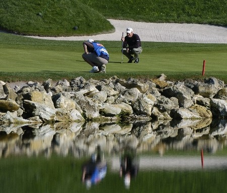 Jeff Maggert and a caddy are a reflection on the 18th hole  as  play in the final holes of the third round continues at  the Bay Hill Invitational March 20, 2005 in Orlando.