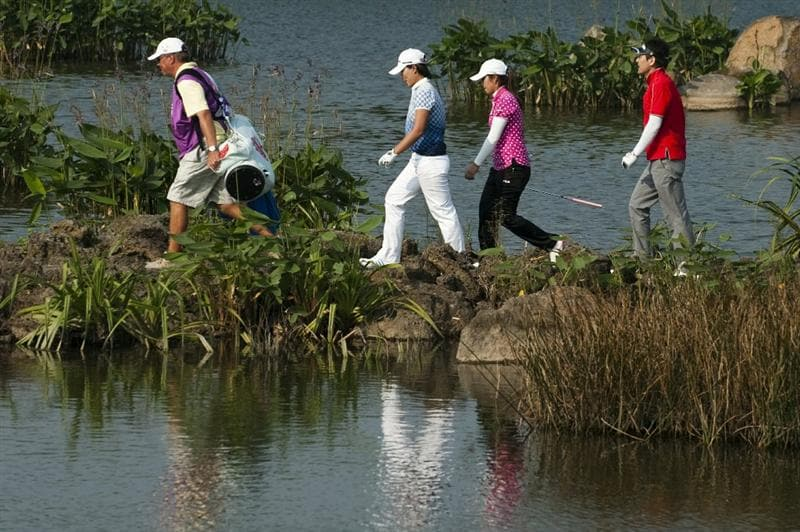 HAIKOU, CHINA - OCTOBER 30:  Se Ri Pak (2nd L), He Yong Choi (2nd R) and Sung Ki Ahn (R) of South Korea walk on the 18th tee during day four of the Mission Hills Start Trophy tournament at Mission Hills Resort on October 30, 2010 in Haikou, China. The Mission Hills Star Trophy is Asia's leading leisure liflestyle event and features Hollywood celebrities and international golf stars.  (Photo by Victor Fraile/Getty Images for Mission Hills)