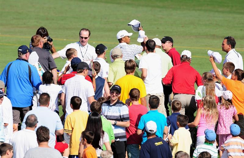AKRON, OH - AUGUST 05:  Tiger Woods of the U.S. throws a hat as he is chased by young fans during a practice round of the World Golf Championship Bridgestone Invitational on August 5, 2009 at Firestone Country Club in Akron, Ohio.  (Photo by Stuart Franklin/Getty Images)