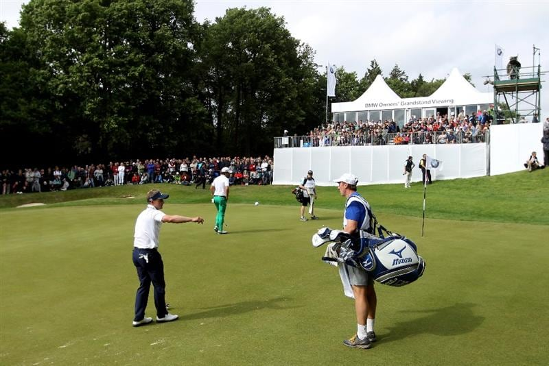 VIRGINIA WATER, ENGLAND - MAY 29:  Luke Donald of England tosses his ball to his caddie on the 13th green during the final round of the BMW PGA Championship  at the Wentworth Club on May 29, 2011 in Virginia Water, England.  (Photo by Warren Little/Getty Images)