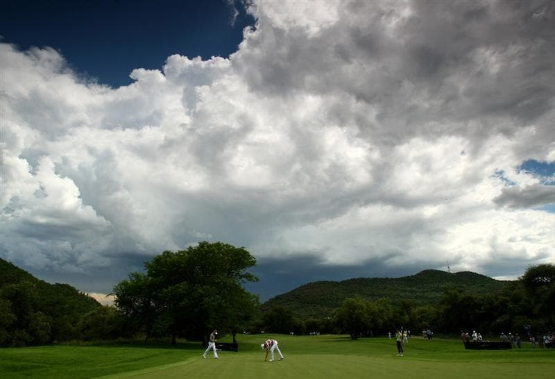 SUN CITY, SOUTH AFRICA - DECEMBER 05:  Luke Donald of England and Robert Karlsson of Sweden putt out on the 11th green as storm clouds gather above the course during the second round of the Nedbank Golf Challenge at the Gary Player Country Club on December 5, 2008 in Sun City, South Africa.  (Photo by Richard Heathcote/Getty Images)