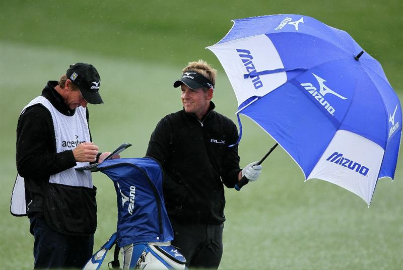 MARANA, AZ - FEBRUARY 27:  Luke Donald of England (R) shields himself from the weather with an umbrella as he waits on the fourth fairway with caddie John McLaren (L) during the final round of the Accenture Match Play Championship at the Ritz-Carlton Golf Club on February 27, 2011 in Marana, Arizona.  (Photo by Andy Lyons/Getty Images)