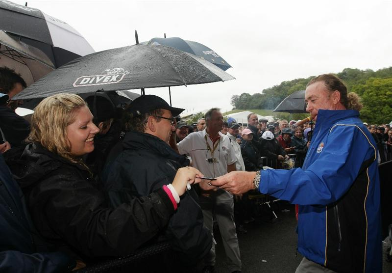 NEWPORT, WALES - OCTOBER 01:  Miguel Angel Jimenez of Europe signs autographs as rain falls and play is suspended during the Morning Fourball Matches during the 2010 Ryder Cup at the Celtic Manor Resort on October 1, 2010 in Newport, Wales.  (Photo by Andrew Redington/Getty Images)