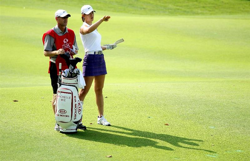 SINGAPORE - FEBRUARY 27:  Michelle Wie of the USA waits with her caddie on the seventh hole during the third round of the HSBC Women's Champions at the Tanah Merah Country Club on February 27, 2010 in Singapore.  (Photo by Andrew Redington/Getty Images)