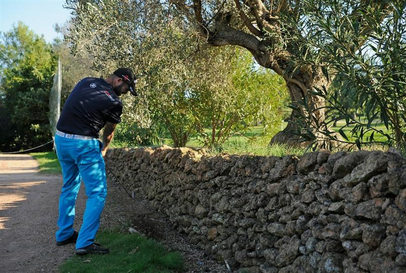 CASTELLON DE LA PLANA, SPAIN - OCTOBER 23:  Christian Nilsson of Sweden plays his approach shot on the 18th hole from a postion by a wall on the 13th tee during the third round of the Castello Masters Costa Azahar at the Club de Campo del Mediterraneo on October 23, 2010 in Castellon de la Plana, Spain.  (Photo by Stuart Franklin/Getty Images)