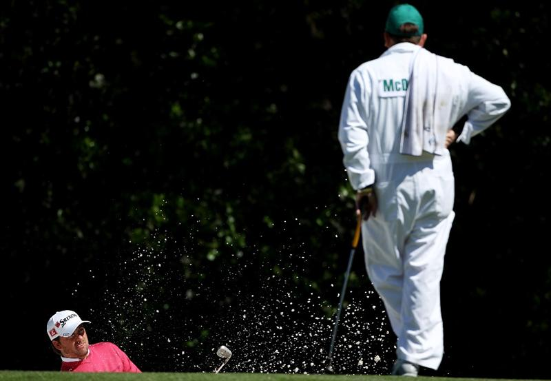 AUGUSTA, GA - APRIL 05:  Graeme McDowell of Northern Ireland plays a bunker shot as his caddie Ken Comboy looks on during a practice round prior to the 2011 Masters Tournament at Augusta National Golf Club on April 5, 2011 in Augusta, Georgia.  (Photo by Andrew Redington/Getty Images)