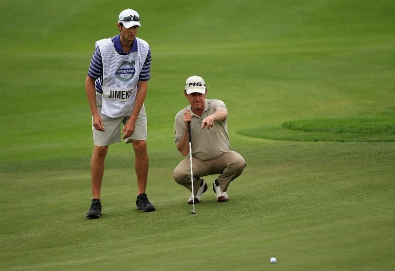 BAHRAIN, BAHRAIN - JANUARY 28:  Miguel Angel Jimenez of Spain lines up a putt with his caddie Michael Hough on the 18th green during the second round of the Volvo Golf Champions at The Royal Golf Club on January 28, 2011 in Bahrain, Bahrain.  (Photo by Andrew Redington/Getty Images)