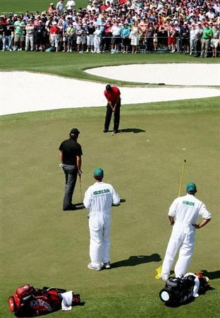 AUGUSTA, GA - APRIL 12:  Tiger Woods putts on the ninth green as Phil Mickelson and their caddies look on during the final round of the 2009 Masters Tournament at Augusta National Golf Club on April 12, 2009 in Augusta, Georgia.  (Photo by David Cannon/Getty Images)