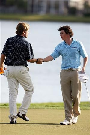 PALM BEACH GARDENS, FL - MARCH 07:  Rory McIlroy shakes the hand of playing Brett Quigley partner after finishing their round on the 18th green in the third round of The Honda Classic at PGA National Resort and Spa on March 7, 2009 in Palm Beach Gardens, Florida.  (Photo by Doug Benc/Getty Images)