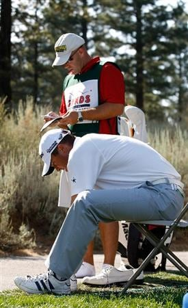 RENO, NV - AUGUST 08:  Ryan Palmer removes his golf spikes and puts on his caddie's, James Edmondson, tennis shoes so as to get better foot grip while hitting his second shot off the cart path during the third round of the Legends Reno-Tahoe Open on August 8, 2009 at Montreux Golf and Country Club in Reno, Nevada.  (Photo by Jonathan Ferrey/Getty Images)