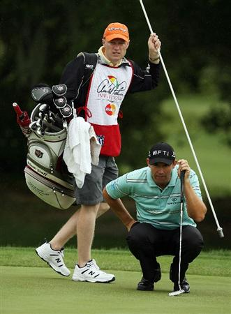 ORLANDO, FL - MARCH 29:  Padraig Harrington of Ireland lines up a putt on the first green alongside his caddie Ronan Flood during the final round of the Arnold Palmer Invitational at the Bay Hill Club & Lodge on March 29, 2009 in Orlando, Florida.  (Photo by Doug Benc/Getty Images)