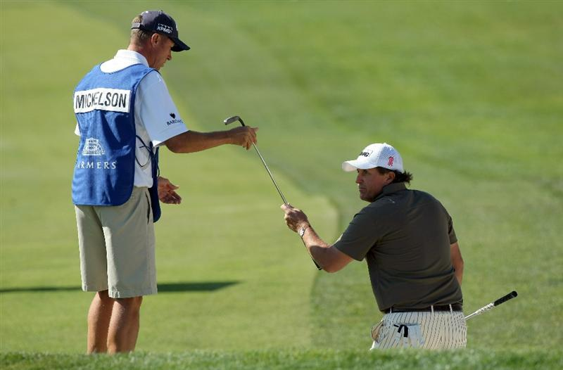 LA JOLLA, CA - JANUARY 29:  Phil Mickelson switches clubs with Jim 'Bones' Mackay after hitting the ball out of the 6th bunker during Round 3 of the Farmers Insurance Open at Torrey Pines on January 29, 2011 in La Jolla, California. (Photo by Donald Miralle/Getty Images)