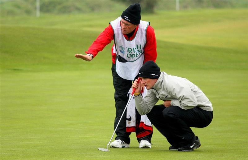 BALTRAY, IRELAND - MAY 14:  Marc Warren of Scotland is given some advice by his caddie John Graham on the 18th hole during the first round of The 3 Irish Open at County Louth Golf Club on May 14, 2009 in Baltray, Ireland.  (Photo by Andrew Redington/Getty Images)