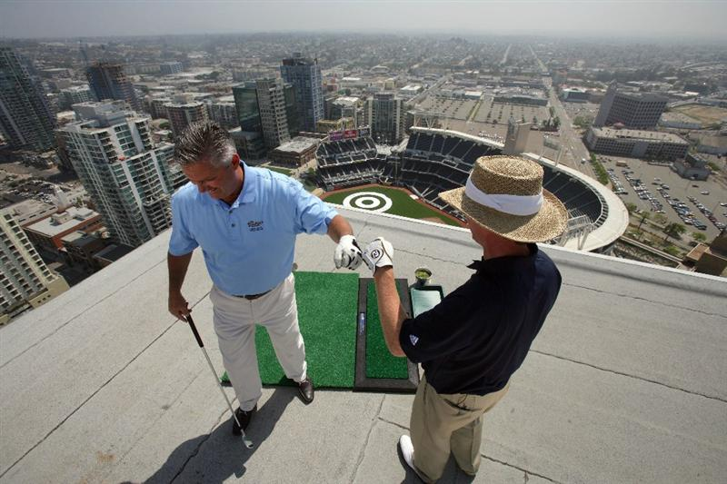 SAN DIEGO - MAY 18: Padres GM Kevin Towers is congratulated by PGA TOUR Player Briny Baird after landing a practice swing off the roof of the Omni Hotel into a bulls-eye planted in right-center field at PETCO Park during the P.F. Chang's Chip for Charity on May 18, 2009 in San Diego, California.  (Donald Miralle/Getty Images )