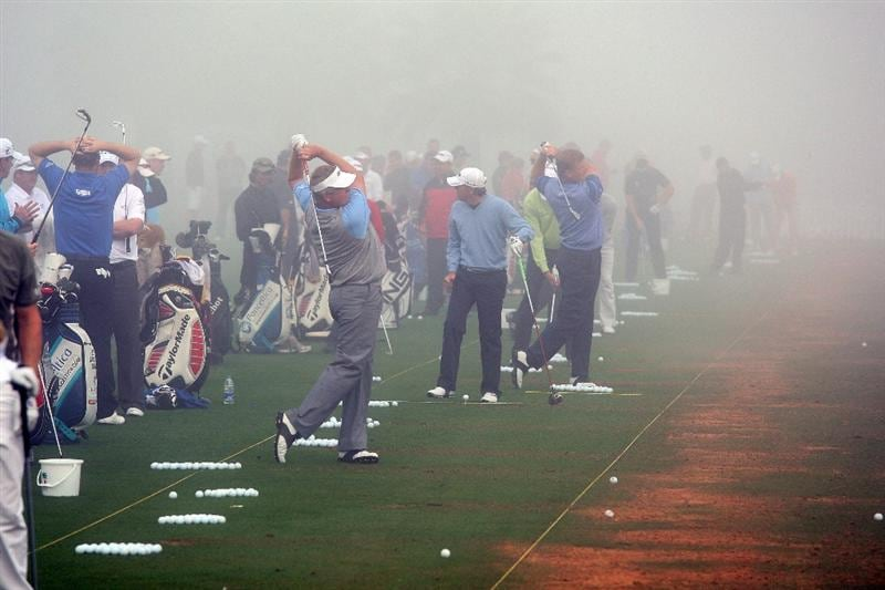 DUBAI, UNITED ARAB EMIRATES - JANUARY 30:  Colin Montgomerie of Scotland and Ernie Els of South Africa both on their follow-throughs are amongst players warming up in the fog that delayed the start by 3 three hours during the completion of the first round of the 2009 Dubai Desert Classic on the Majilis Course at the Emirates Golf Club on January 30, 2009 in Dubai, United Arab Emirates.  (Photo by David Cannon/Getty Images)
