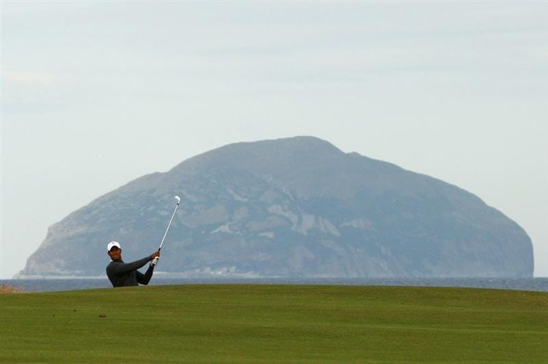 TURNBERRY, SCOTLAND - JULY 14:  Tiger Woods of USA hits a shot in front of Ailsa Craig during a practice round prior to the 138th Open Championship on July 14, 2009 on the Ailsa Course, Turnberry Golf Club, Turnberry, Scotland.  (Photo by Ross Kinnaird/Getty Images)