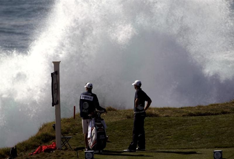 PEBBLE BEACH, CA - FEBRUARY 14:  Dustin Johnson and his caddie look at the breaking surf before Johnson tees off on the eighth hole during the final round of the AT&T Pebble Beach National Pro-Am at Pebble Beach Golf Links on February 14, 2010 in Pebble Beach, California.  (Photo by Ezra Shaw/Getty Images)