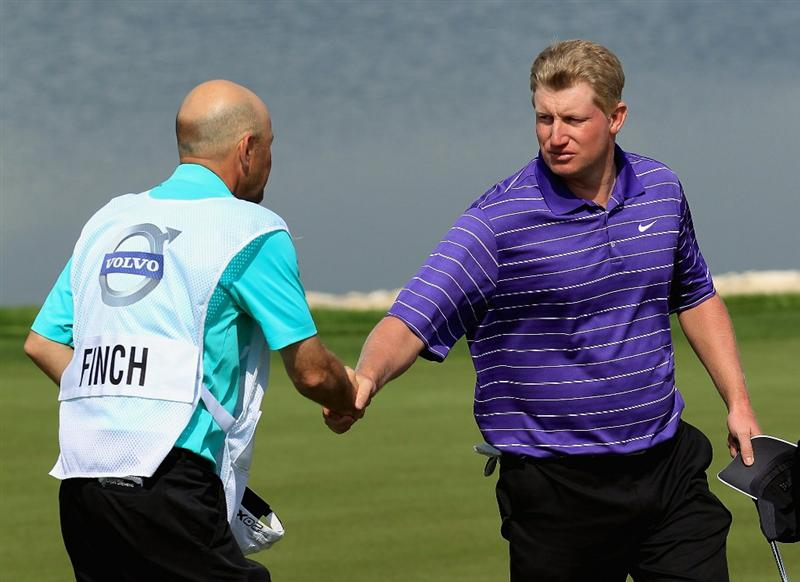 BAHRAIN, BAHRAIN - JANUARY 30:  Richard Finch of England is congratulated by hs caddie on the 18th green after shooting 63 during the final round of the Volvo Golf Champions at The Royal Golf Club on January 30, 2011 in Bahrain, Bahrain.  (Photo by Andrew Redington/Getty Images)