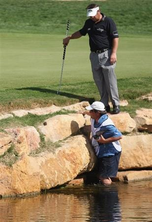VILAMOURA, PORTUGAL - OCTOBER 16:  Emanuele Canonica of Italy helps his caddie in the rescue of a pigeon from the water around the 18th green during the first round of the Portugal Masters at the Oceanico Victoria Golf Course on October 16, 2008 in Vilamoura, Portugal.  (Photo by Warren Little/Getty Images)