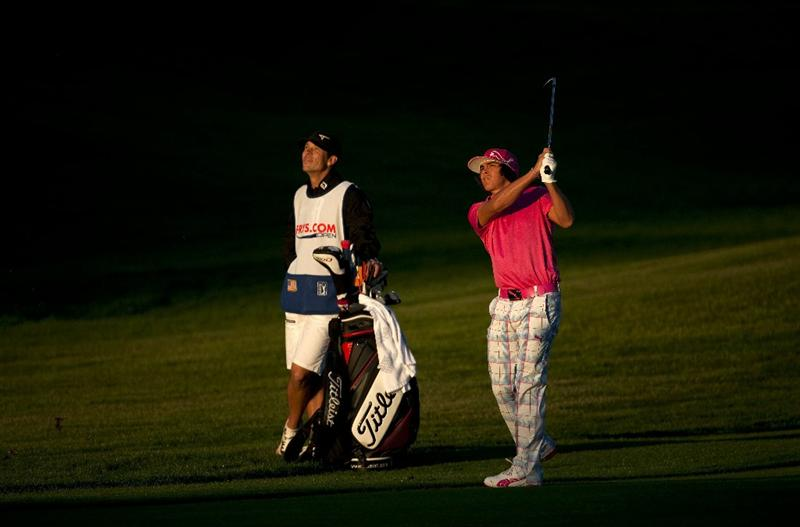 SAN MARTIN, CA - OCTOBER 14:  Rickie Fowler makes an approach on the 10th fairway as his caddie Joe Skovron looks on during the first round of the Frys.com Open at the CordeValle Golf Club on October 14, 2010 in San Martin, California.  (Photo by Robert Laberge/Getty Images)