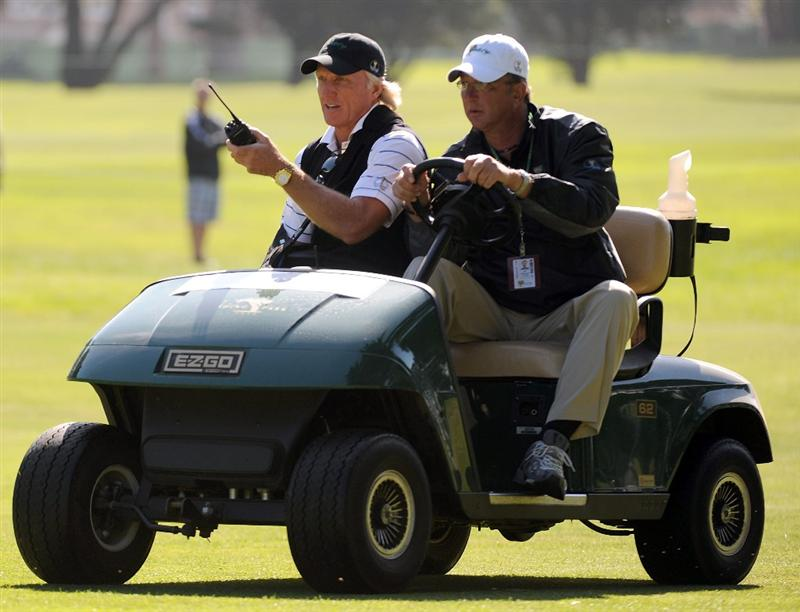 SAN FRANCISCO - OCTOBER 07:  International Team Captain Greg Norman (L) gets a ride from Joe Damiano during a practice round prior to the start of The Presidents Cup at Harding Park Golf Course on October 7, 2009 in San Francisco, California.  (Photo by Harry How/Getty Images)