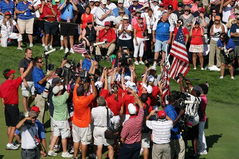SUGAR GROVE, IL - AUGUST 23: The USA team surrounded by photographers and televison cameras celebrate on the 18th fairway during the Sunday singles matches at the 2009 Solheim Cup Matches, at the Rich Harvest Farms Golf Club on August 23, 2009 in Sugar Grove, Ilinois (Photo by David Cannon/Getty Images)